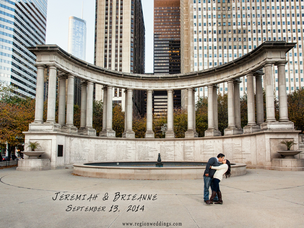 A groom to be dips his fiancé lovingly in front of the Centennial Park fountain in Chicago, Illinois for their engagement photo.