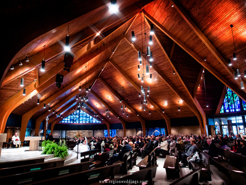 A wide angle photo of a wedding ceremony at Our Lady of Grace Church in Highland, Indiana.