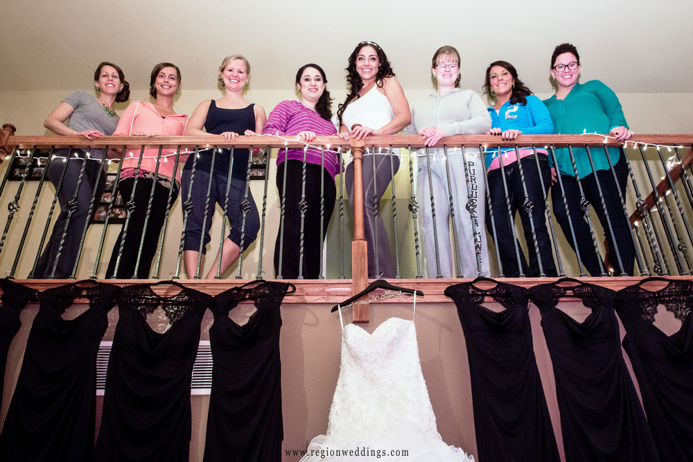 A bridesmaid group photo on a balcony with dress hung beneath them.