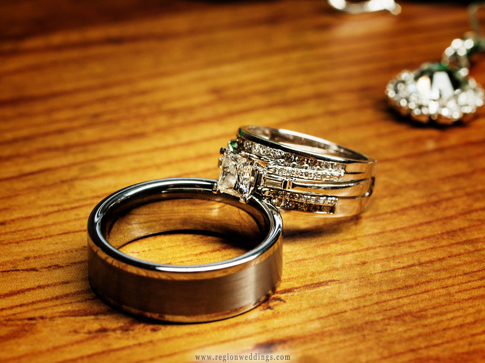 Wedding rings placed together on a wooden dresser top.
