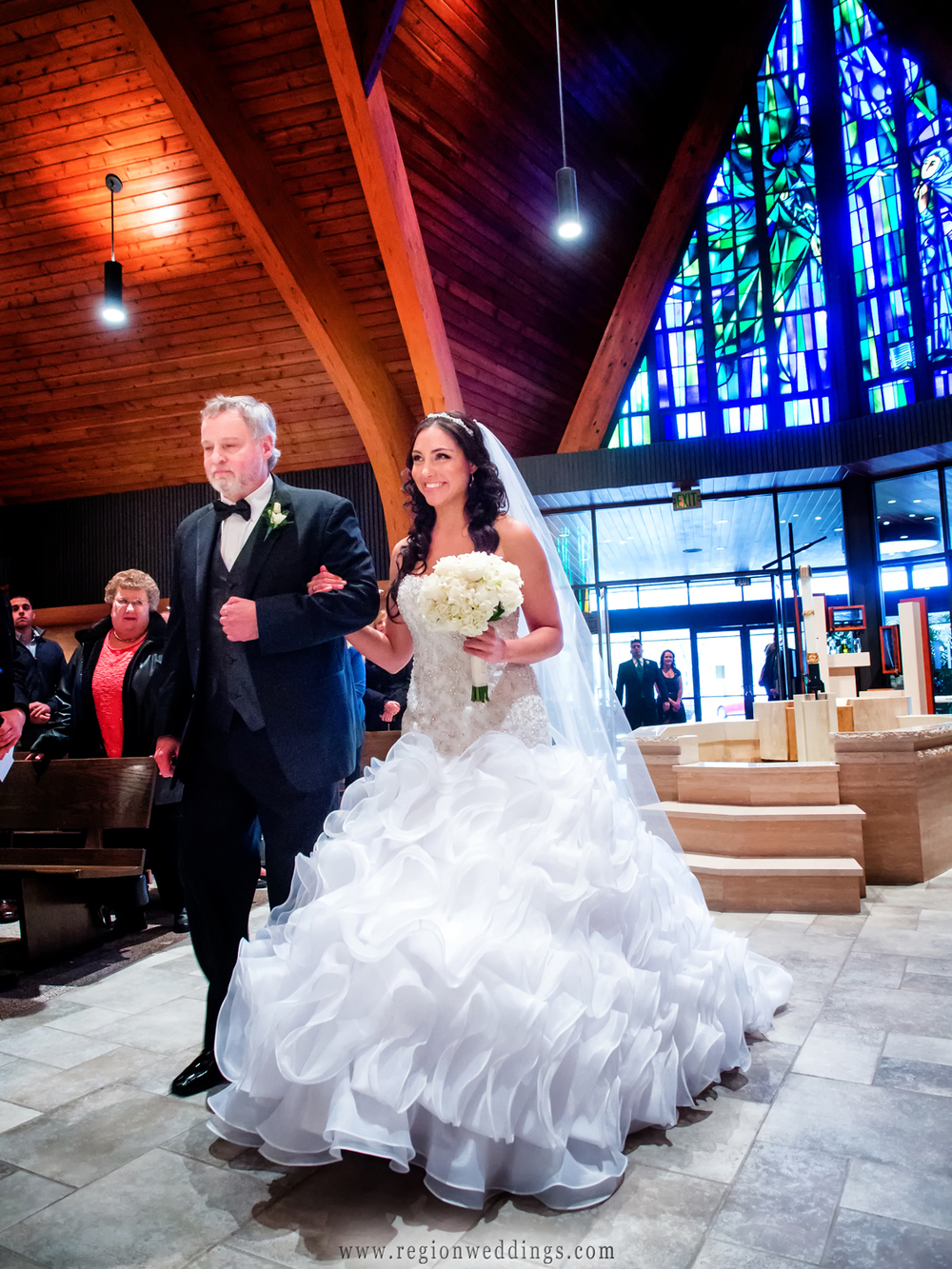 A bride walks down the aisle with her Dad at Our Lady of Grace Church.