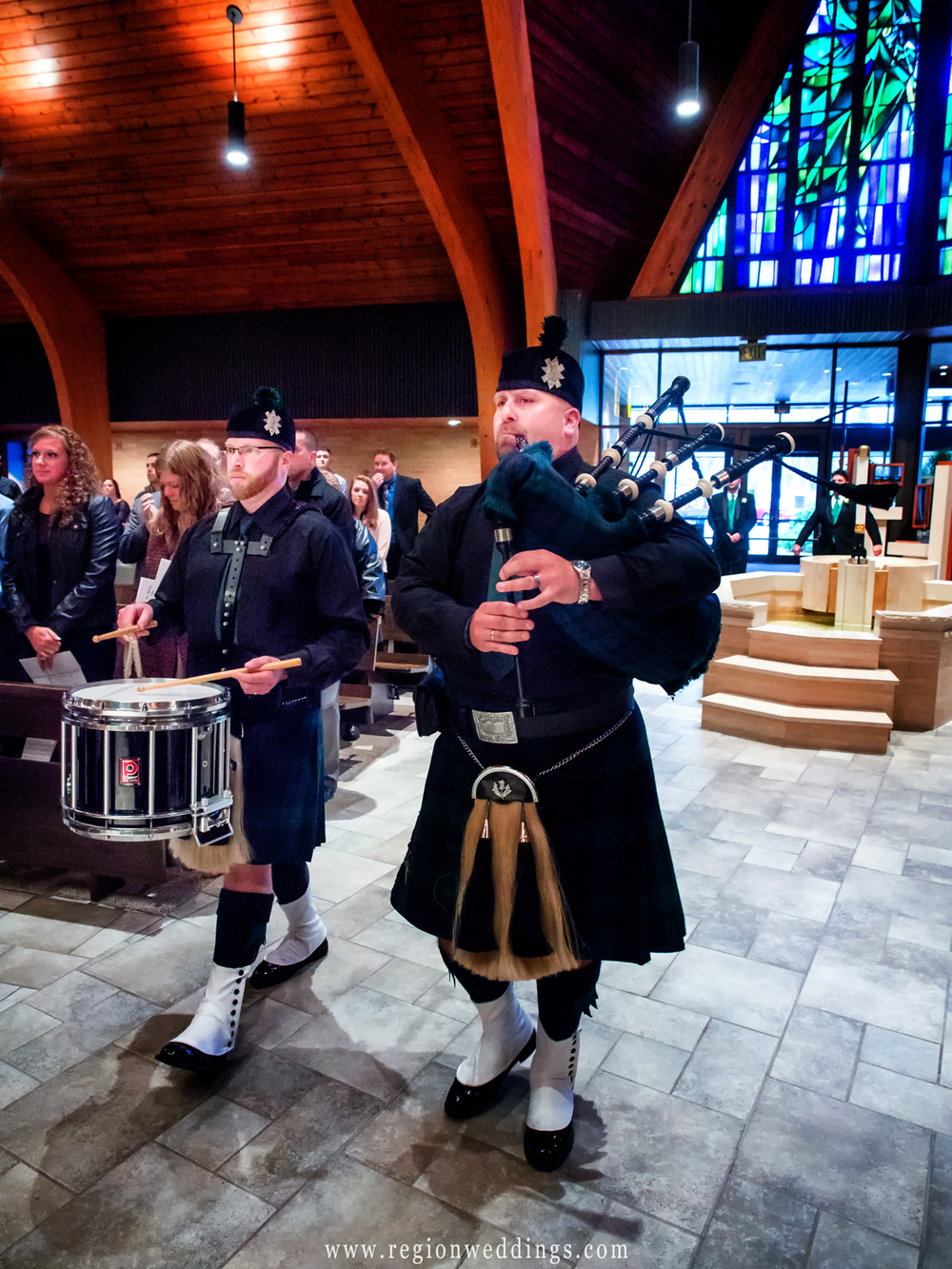 Men in kilts play bag pipes at a wedding at a Catholic church.
