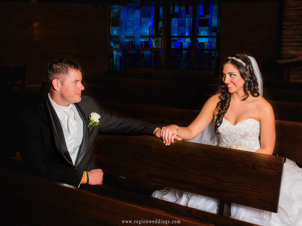 The bride and groom gaze at each other lovingly as they sit in the pews at Our Lady of Grace Church.