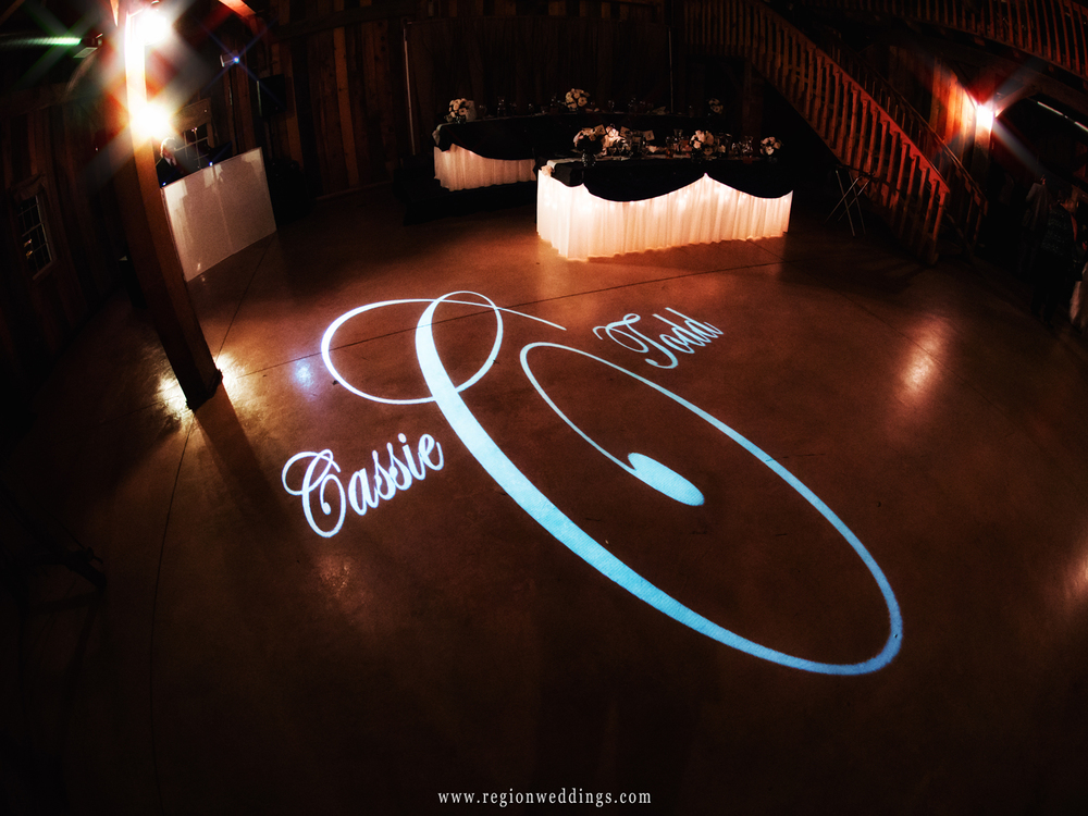 The bride and grooms names are cast as a lighted monogram on the dance floor at a wedding reception at County Line Orchard.