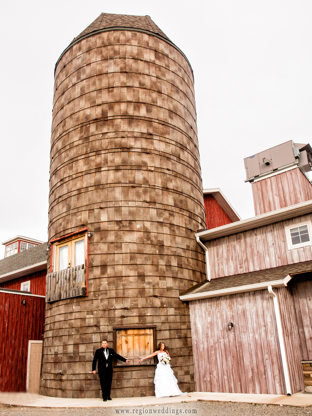 A bride and groom take their first look underneath the silo at County Line Orchard.