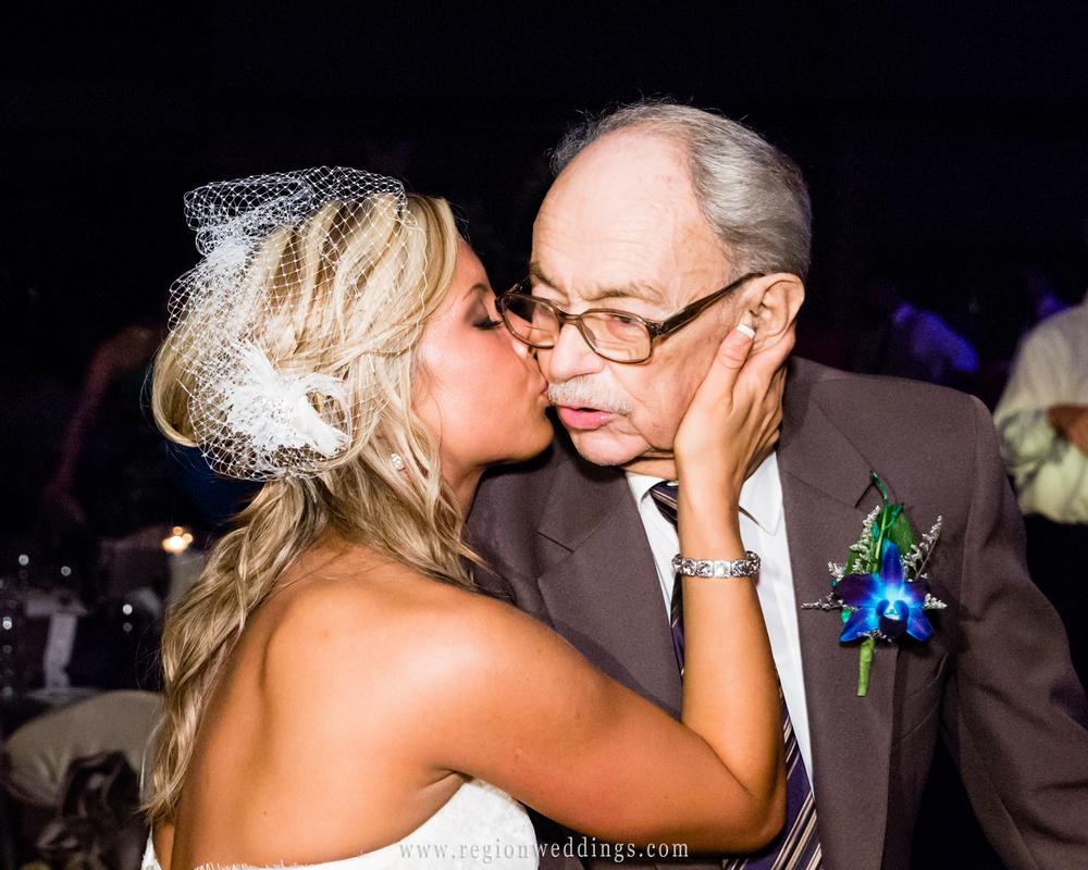Bride kisses grandpa on the dance floor of her wedding reception captured in a candid wedding photo.