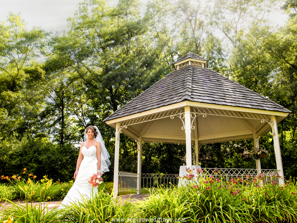 Rays of sun shine upon the bride in front of the gazebo before her outdoor summer wedding ceremony.