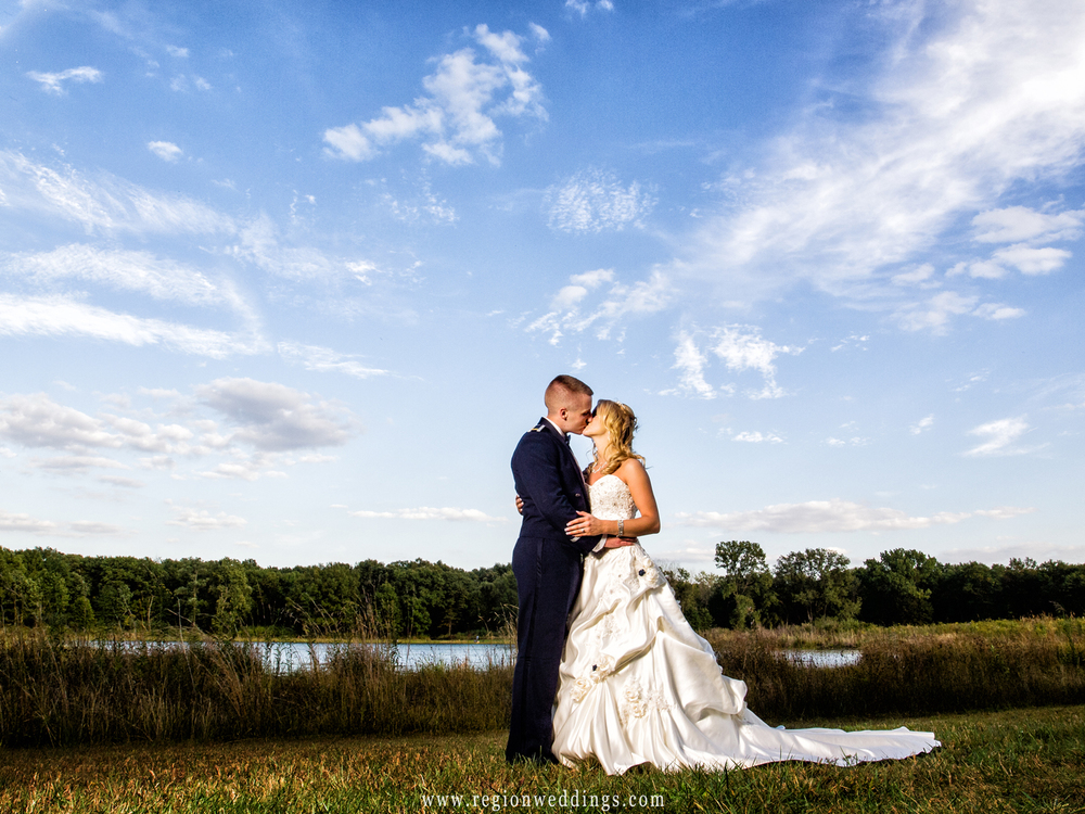 Bride and groom kiss underneath blue skies at Oak Ridge Prairie Park in Griffith, Indiana.
