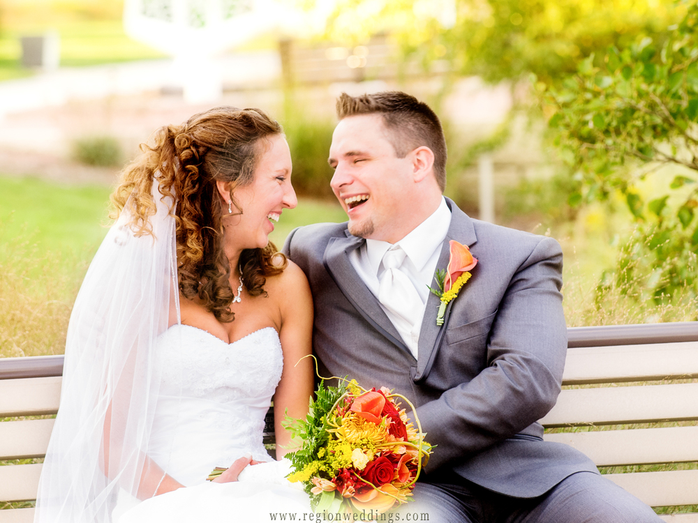 Bride and groom share a laugh on a park bench after their outdoor wedding at Munster's Centennial Park.