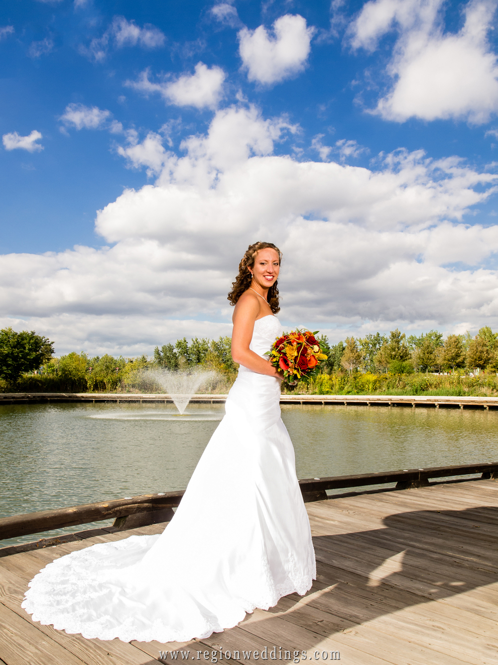 Bride poses with her bouquet of flowers with a fountain behind her and a beautiful blue sky.
