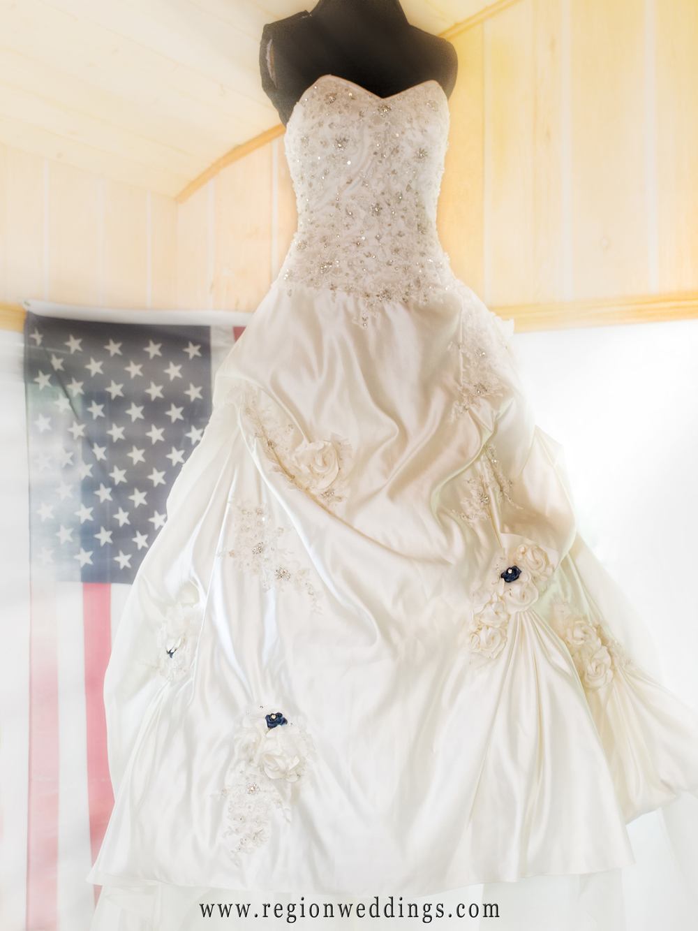 The american flag is seen in the background as the bride's dress hangs in waiting.