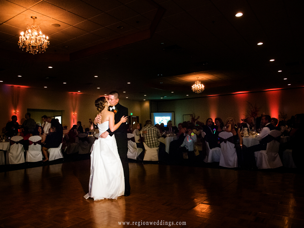 The bride and groom dance at The Patrician Banquet Hall with soft amber lighting in the background.