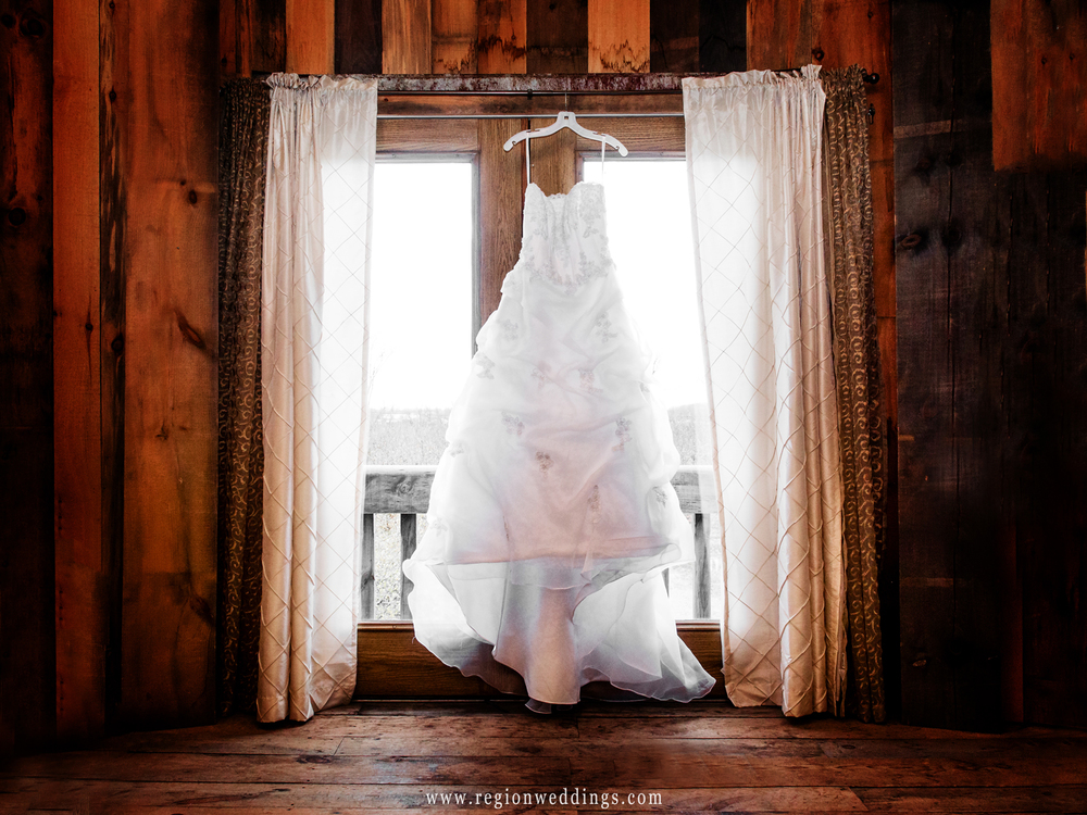 A wedding dress hangs inside a rustic looking barn on wedding day.