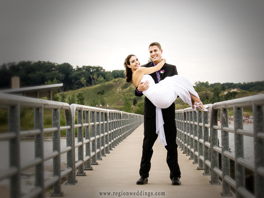The groom carries his bride across the bridge at Portage River Walk.
