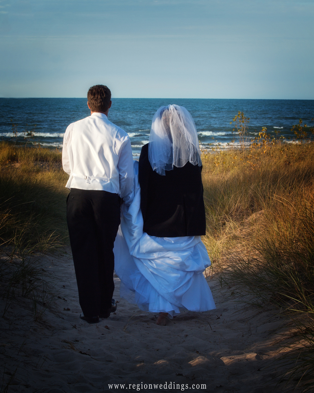 Bride and groom walk toward the beach after their wedding at the Indiana Dunes Lakeshore.