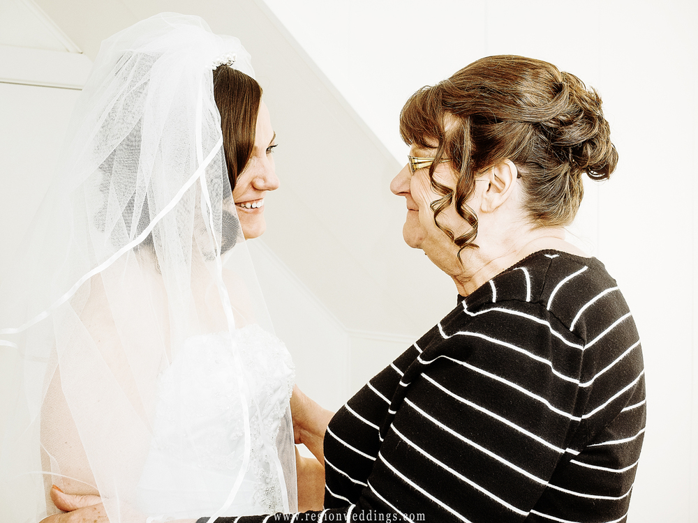 Tender moment between mom and daughter as the bride gets into her wedding dress.