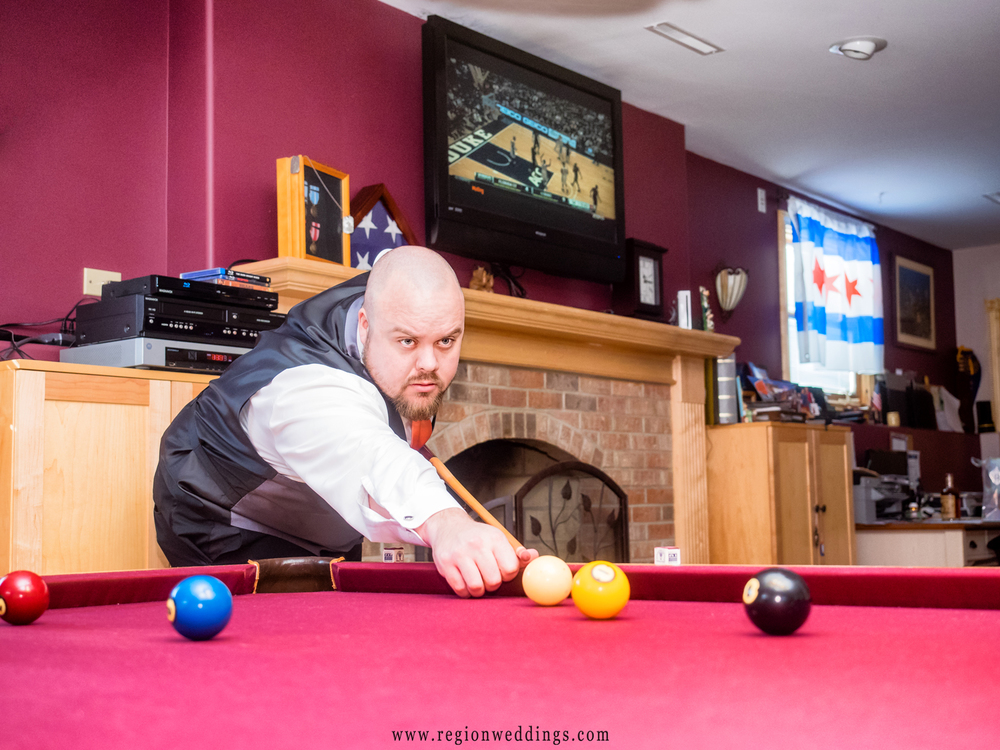 Groomsman gets ready to sink a solid ball in a game of pool on wedding day.