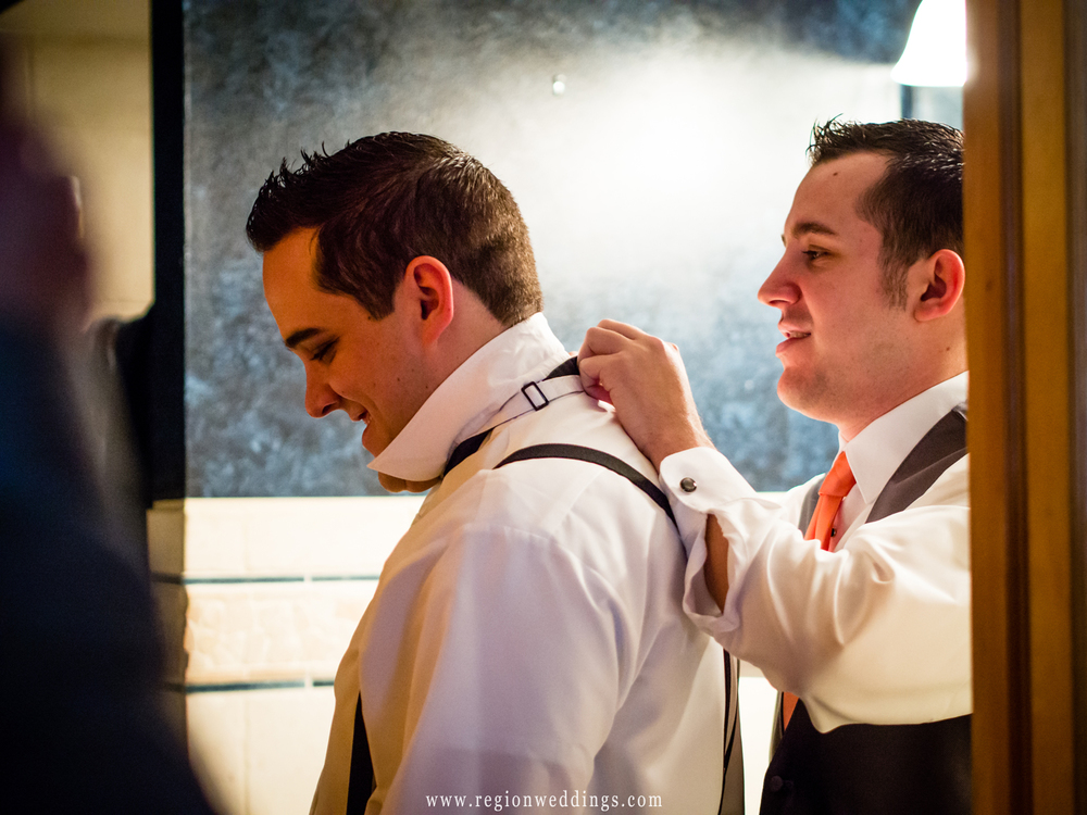 The best man helps out the groom with his tie the morning of the wedding.