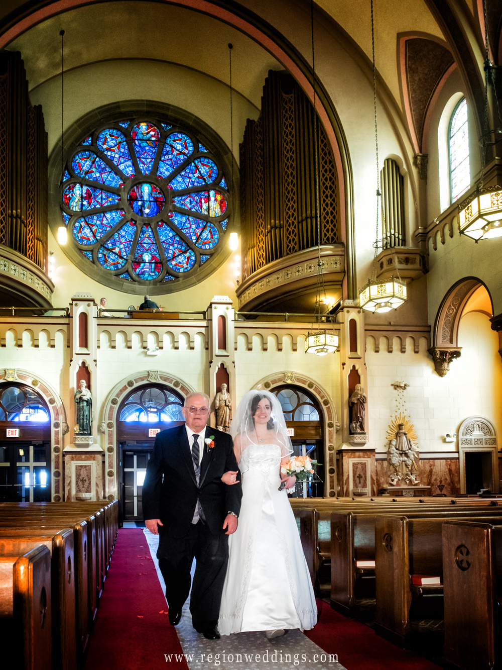 Father and daughter walk down the aisle at Saint Andrew the Apostle Parish.