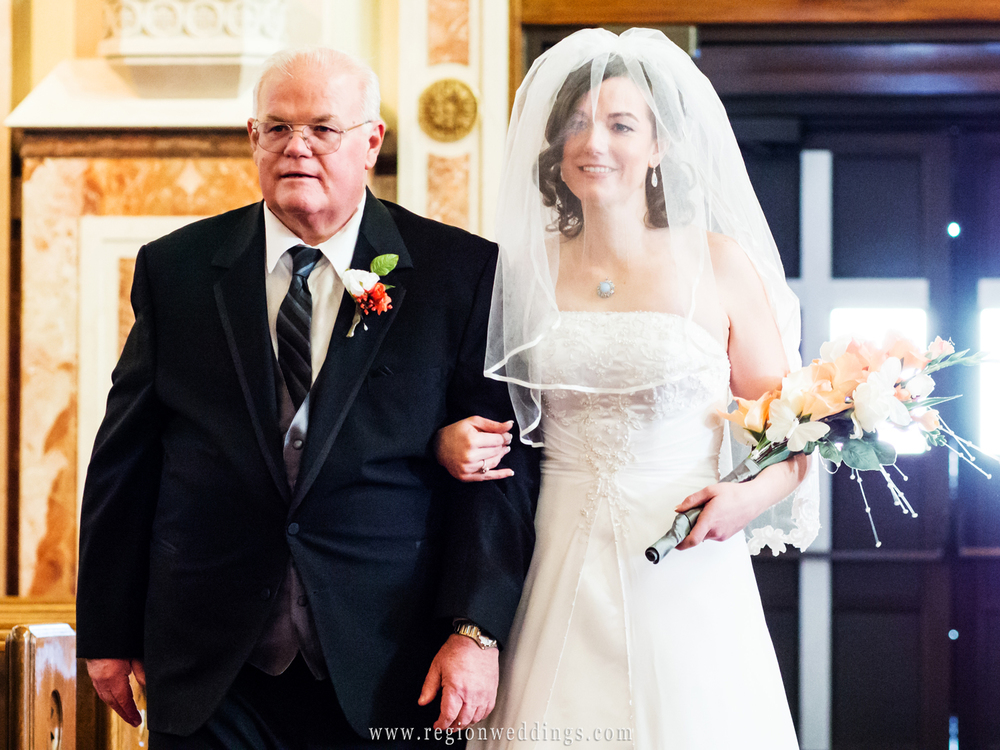 Dad proudly walks his daughter down the aisle at a Catholic wedding in Chicago.