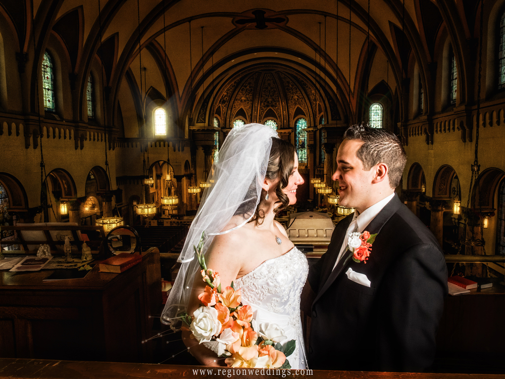 Bride and groom gaze at each other in the balcony overlooking the majestic church.
