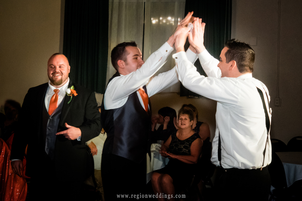 The best man high fives the groom after catching the garter.