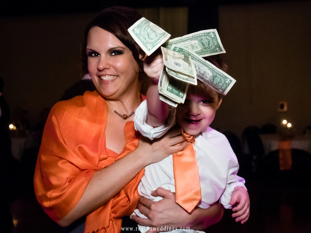 The ring bearer helps out during the dollar dance at Great Oaks Banquet Hall in Cedar Lake, Indiana.