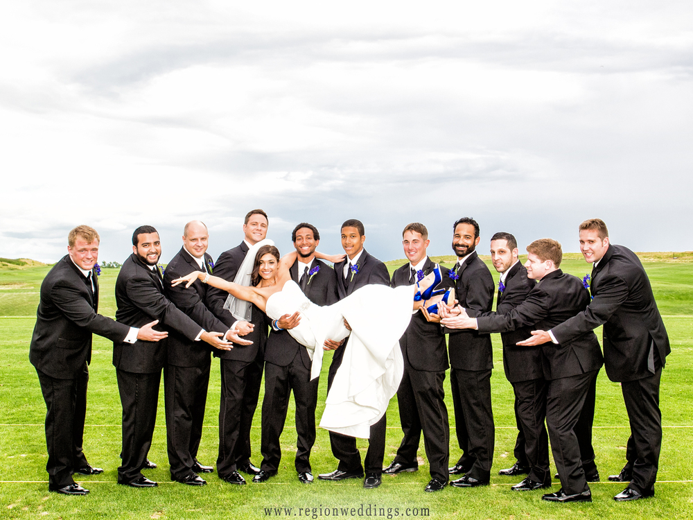 Groomsmen hold the bride aloft at Centennial Park in Munster, Indiana.