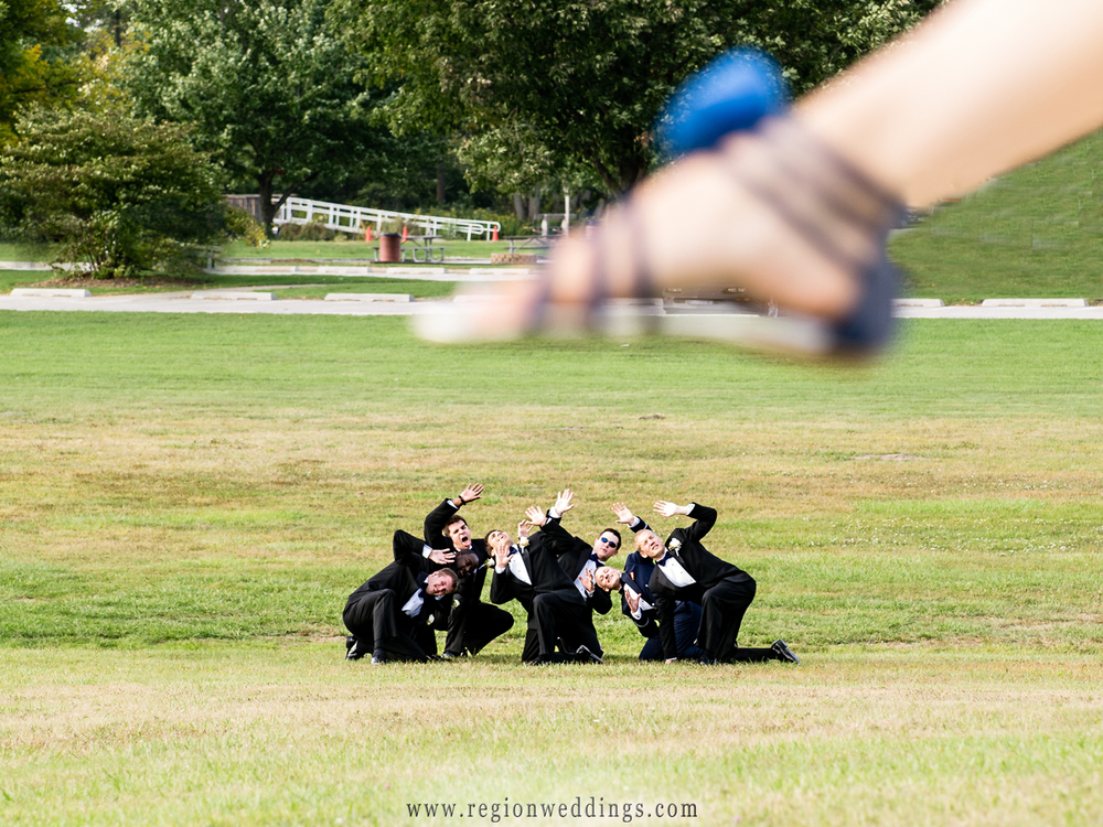 Bride attempts to crush the groomsmen with her blue wedding shoes.
