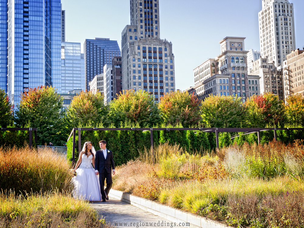 The bride and group walk through the Millennium Park gardens with the tall buildings of Chicago in the background.