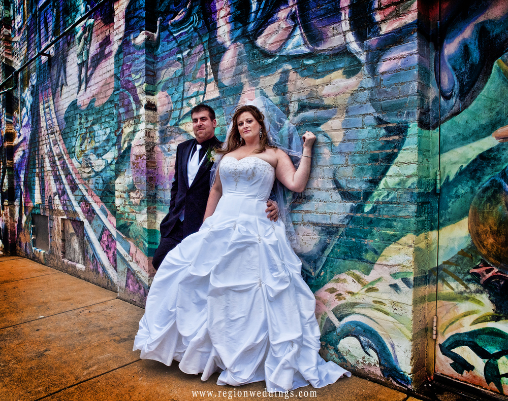 Bride and groom lean against a graffiti wall in downtown Hobart.