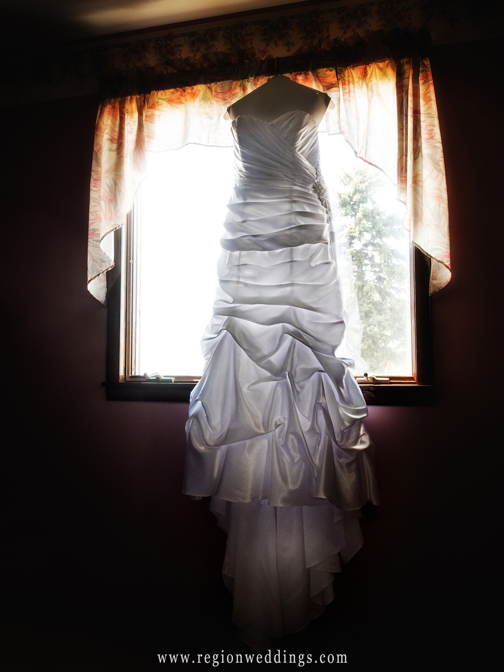 The wedding dress awaits the bride as it hangs in front of a window.