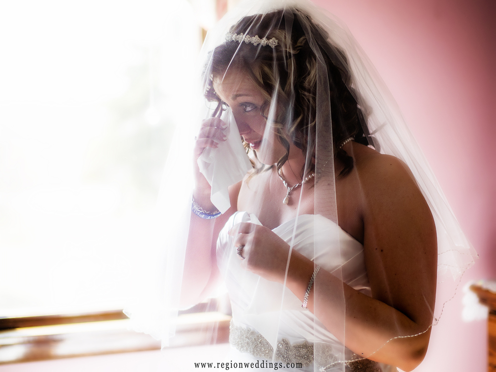 The bride wipes away tears in an emotional moment while getting ready for her wedding.