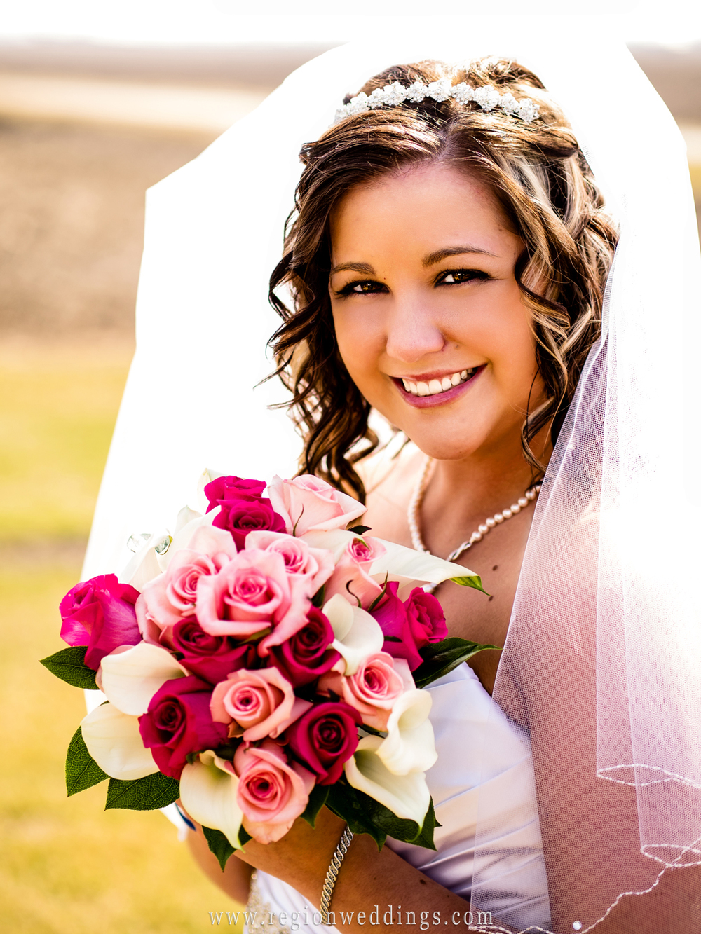 An outdoor wedding portrait of a bride before her Spring wedding holding her pink bouquet of flowers.