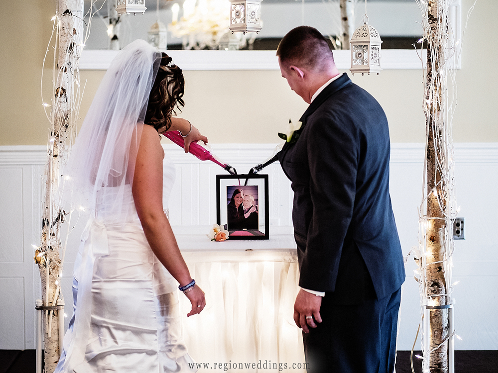 The bride and groom pour sand into a picture frame during their wedding ceremony.