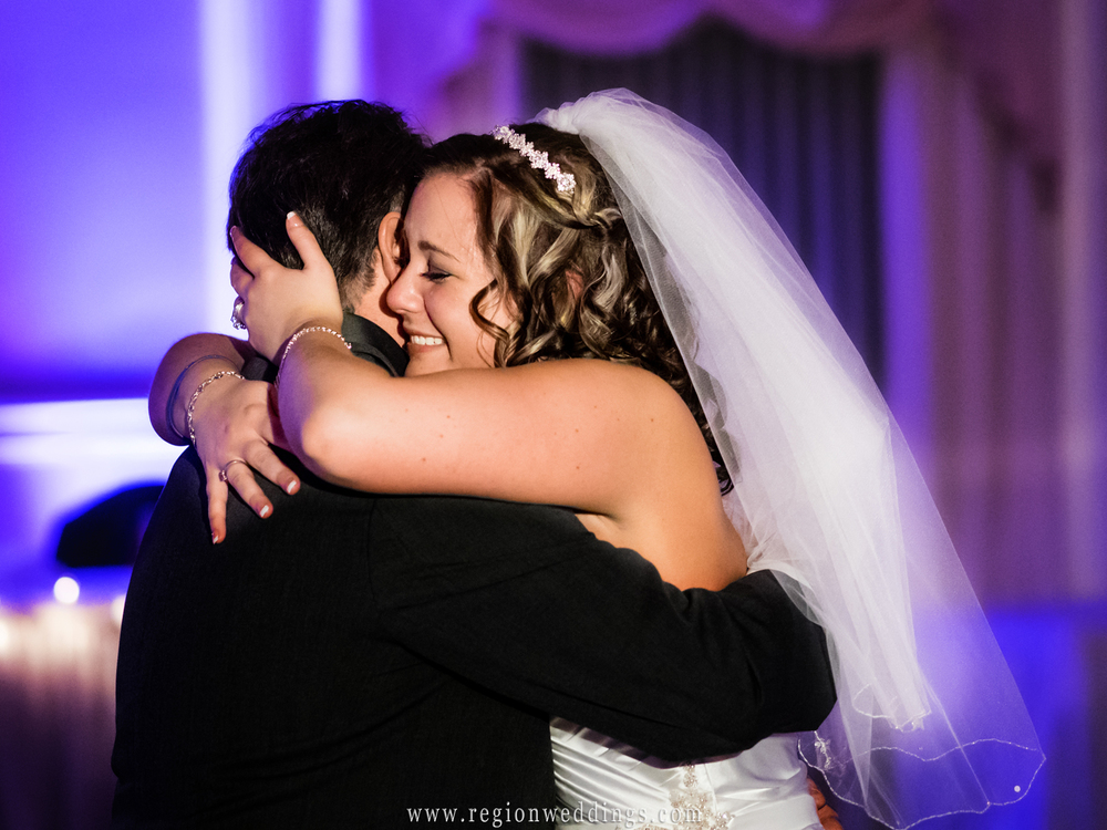 Father and daughter hug emotionally at a wedding reception at The Dream Palace.