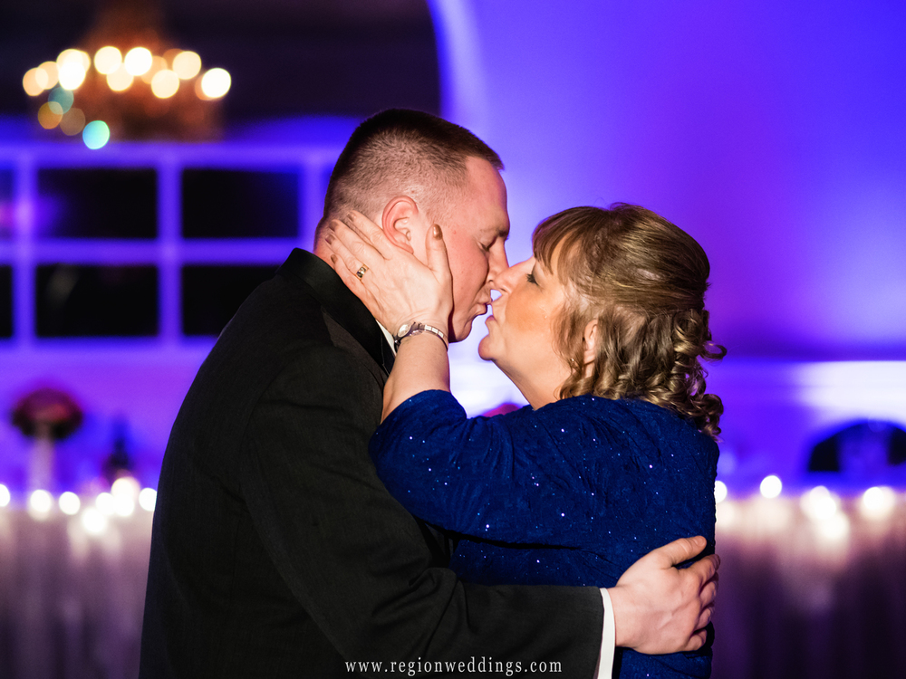 Mom give her son the groom a kiss on the dance floor at his wedding reception.