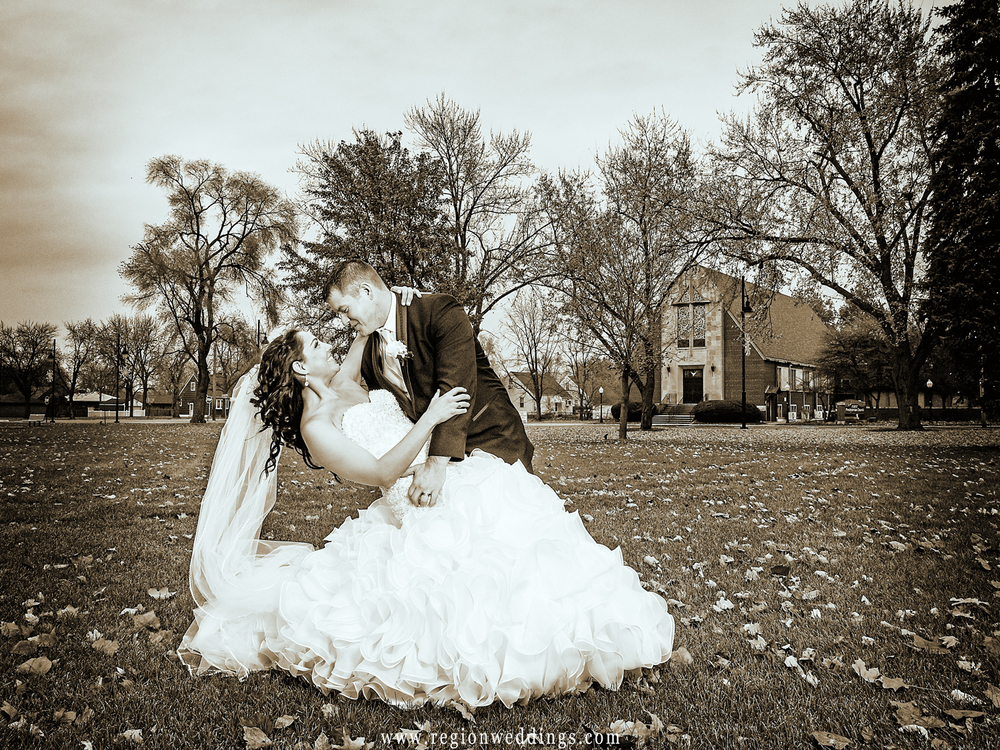 The groom dips his bride in front of Our Lady of Grace Church in Highland, Indiana.