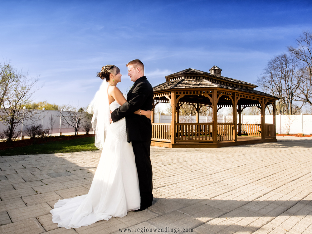 The bride and groom gaze at each other in front of the gazebo after their Spring wedding.