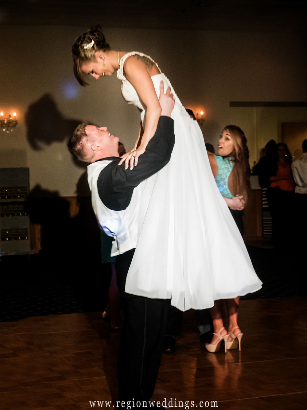 The groom lifts his bride triumphantly into the air at their wedding reception at The Patrician.