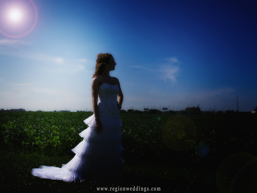 A bride alone in silhouette with a sunburst at an Indiana farm.