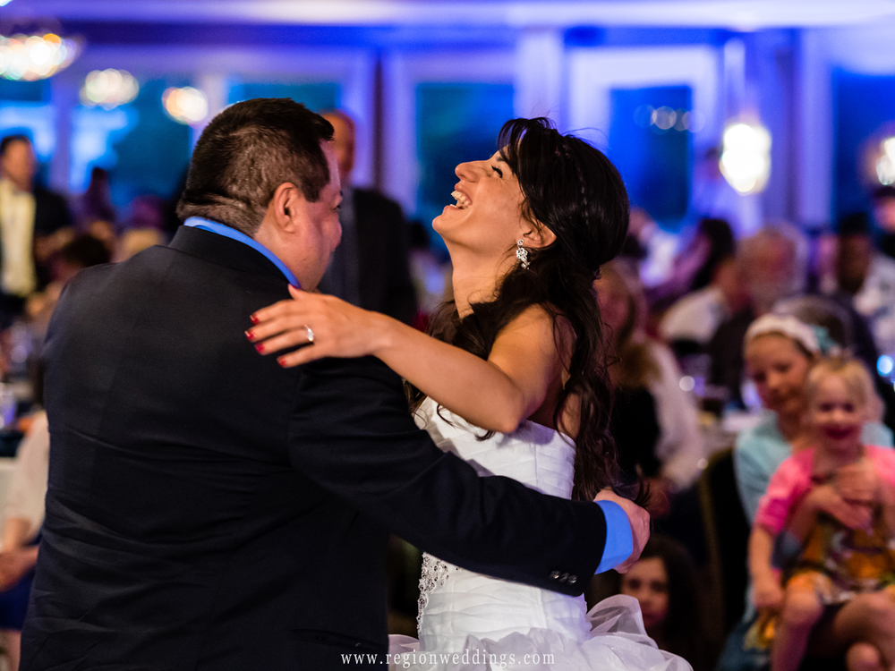The bride laughs with joy while dancing with her father.
