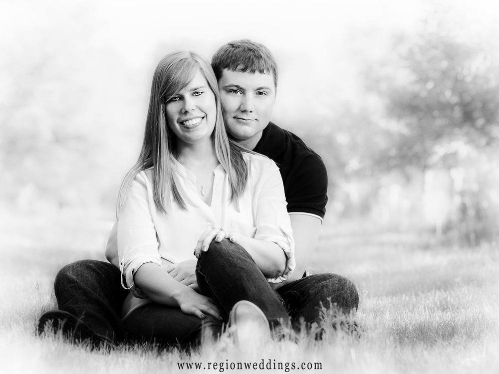 A soft focus black and white engagement photo of a couple snuggling in the grass engulfed in sunlight.
