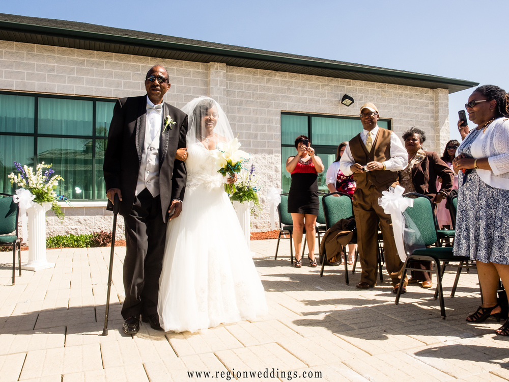 The bride walks down the aisle at her outdoor wedding along side her Father.