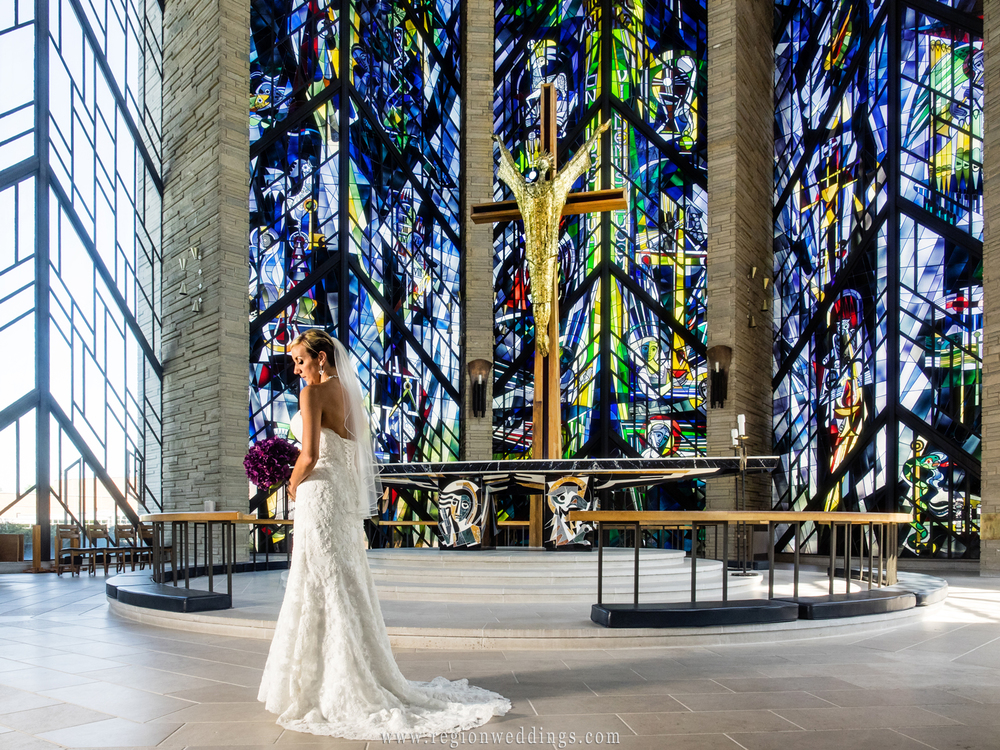 The bride alone at the altar in front of stained glass windows.