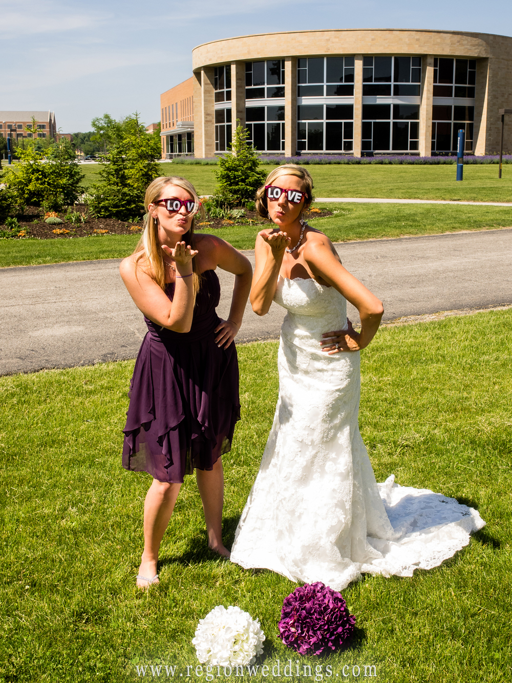 The bride and her bridesmaid blow kisses to the camera.