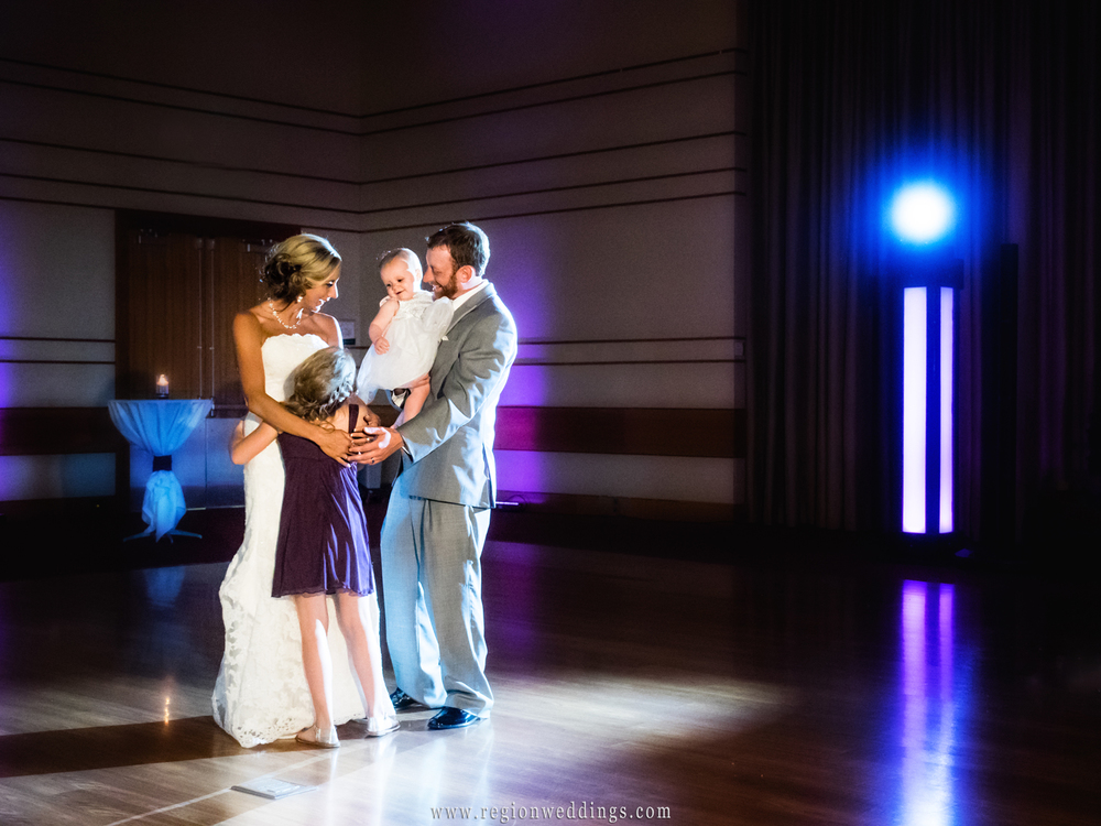 The bride and groom invite their children onto the floor for the first dance at their wedding reception.