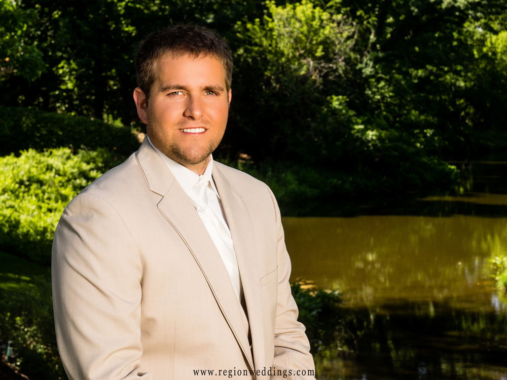 Groom sits by the ledge of a river near Aberdeen Manor.