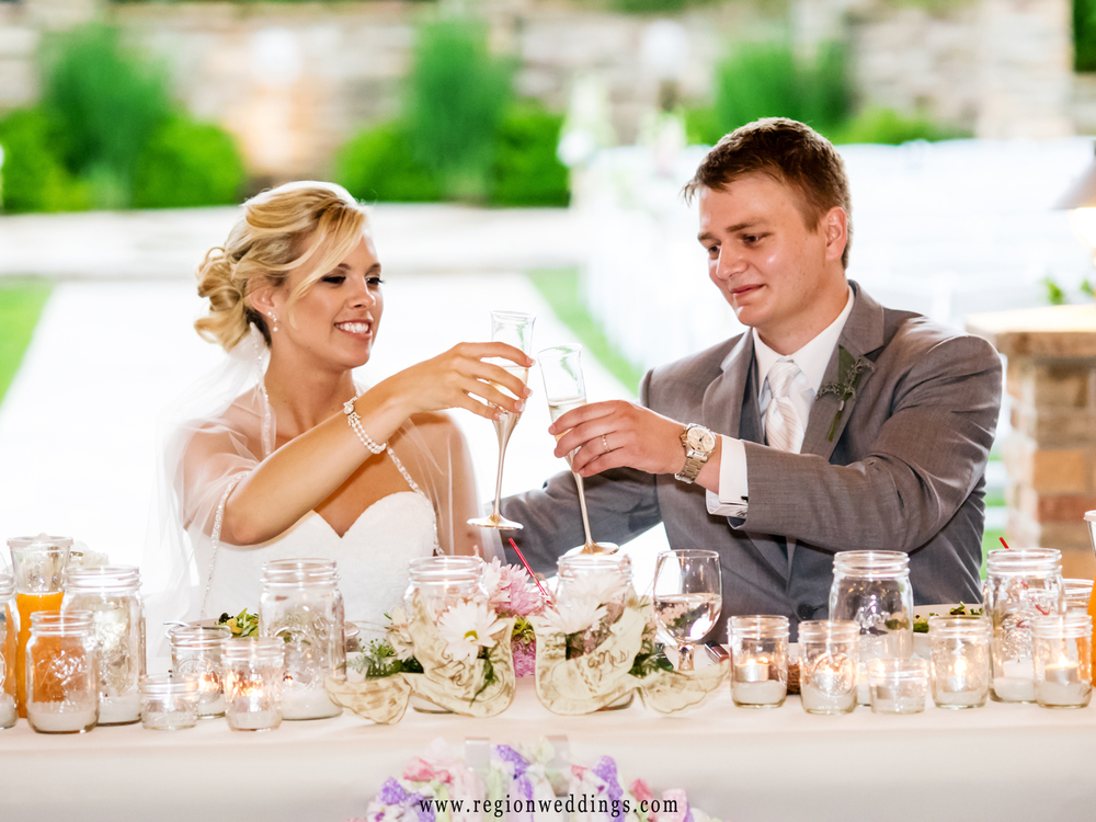 The bride and groom drink champagne at Sandy Pines Pavilion during their wedding reception.