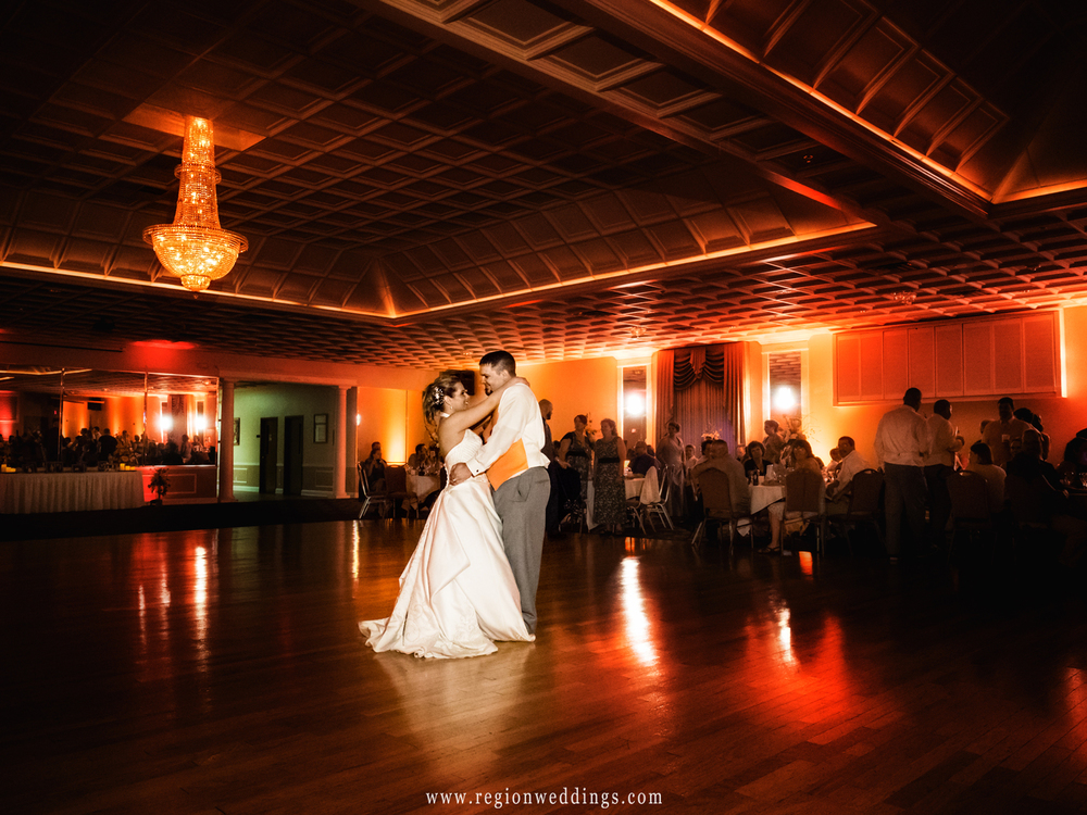 The bride and groom take their first dance at Macedonian Hall in Crown Point, Indiana surrounded by amber lighting.